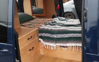 woodwork and bed in ford transit 350 custom camper van conversion in golden, colorado